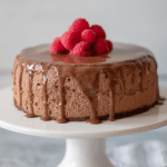 Keto Instant Pot Chocolate Cheesecake on a white cake stand topped with fresh raspberries
