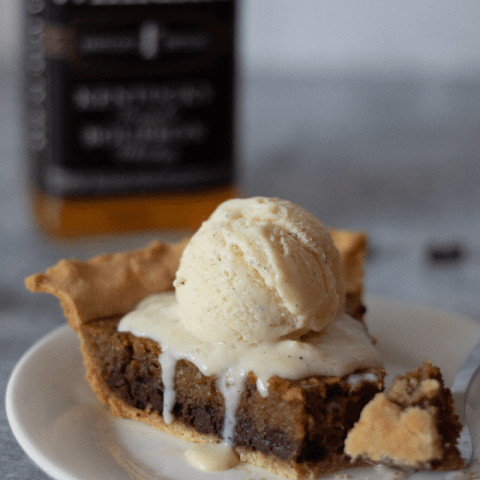 A slice of keto Kentucky Derby Pie topped with vanilla ice cream. There is a bottle of bourbon and pecans in the background.
