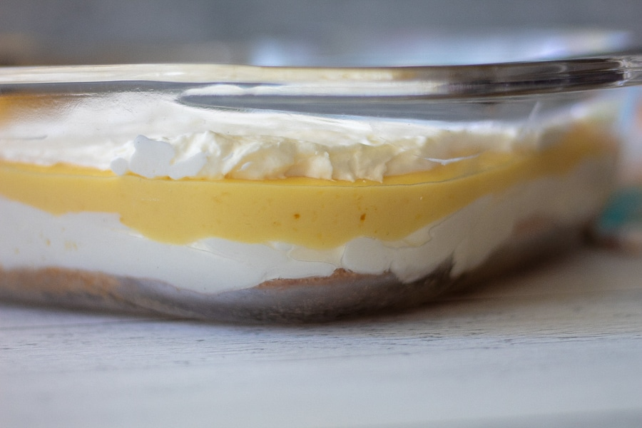 A side view of keto lemon lush dessert with 4 layers in a glass dish