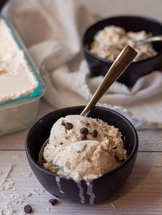 Keto coconut chip ice cream in a black bowl topped with sugar free chocolate chips and coconut flakes