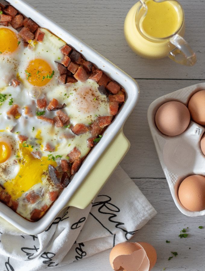 an overhead photo of keto eggs benedict casserole with brown eggs off to the side
