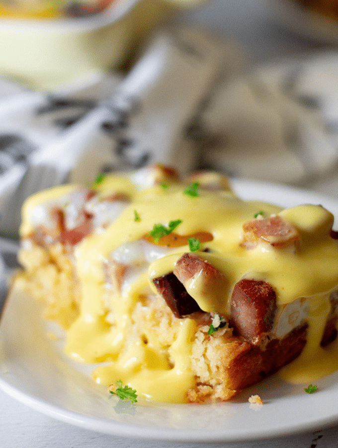 a slice of keto eggs benedict casserole on a white plate topped with easy hollandaise