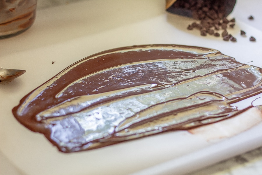Melted sugar free chocolate spread into a thin layer on parchment paper to make chocolate pieces for keto ice cream