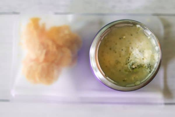 a thermos filled with broccoli and cheese soup, with Parmesan cheese crackers on the side