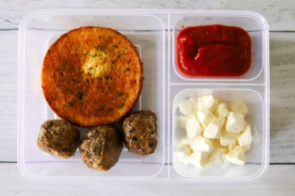 a lunch box packed with meatballs, mozzarella cheese, marinara, and a toasted smart bun.