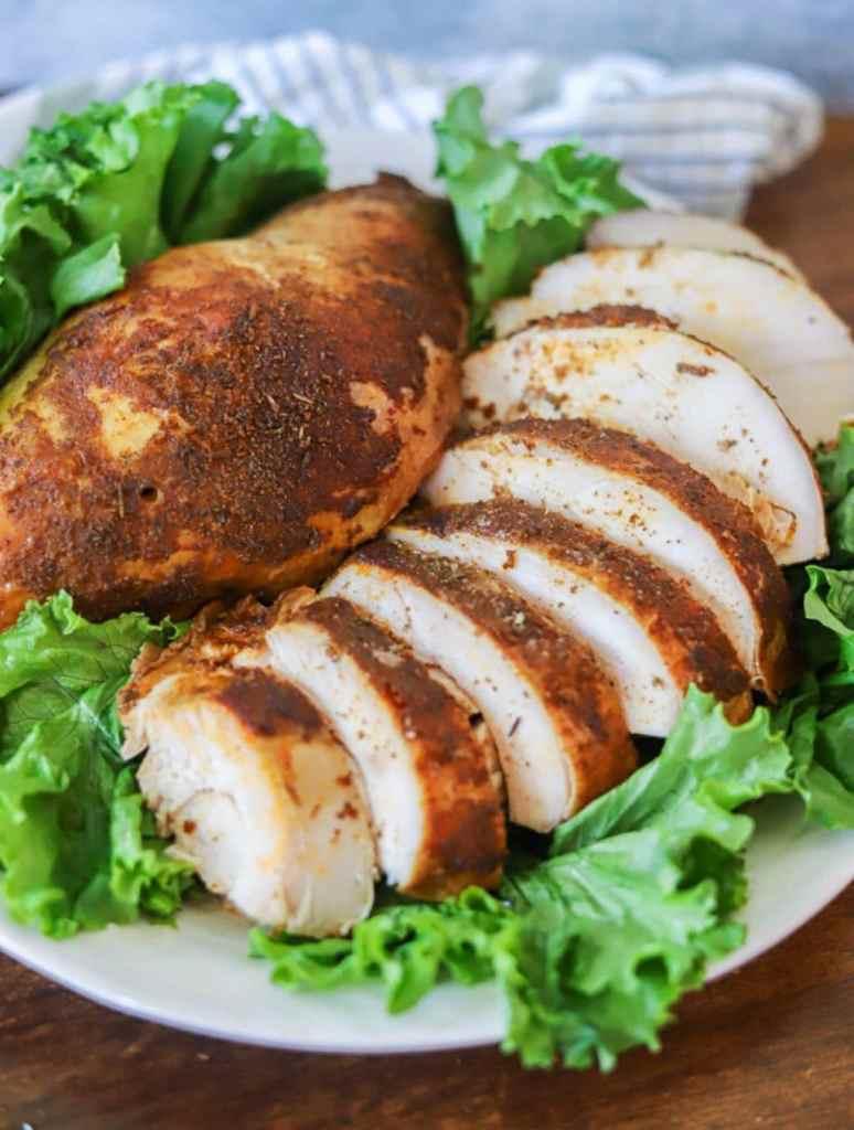 sliced turkey breast on a platter garnished with green leafy lettuce