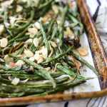 Close up of roasted green beans with almonds on a sheet pan