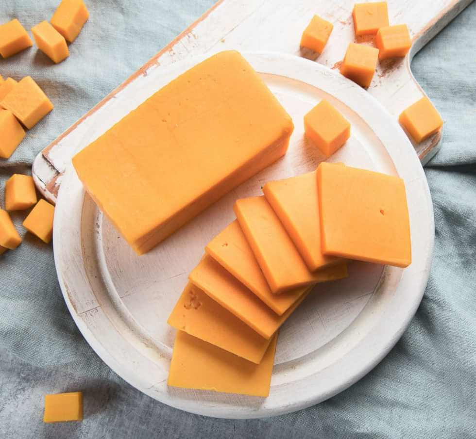Cheddar cheese block and slices on a white plate