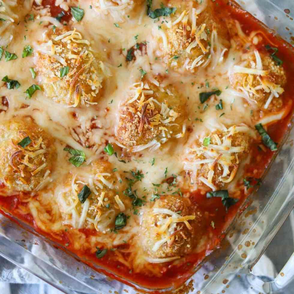 Chicken meatballs in a baking dish with marinara sauce and melted cheese