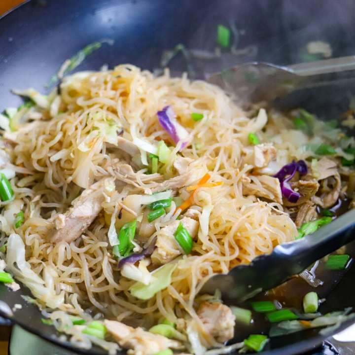 Shiritaki noodles and vegetables being cooked in a wok