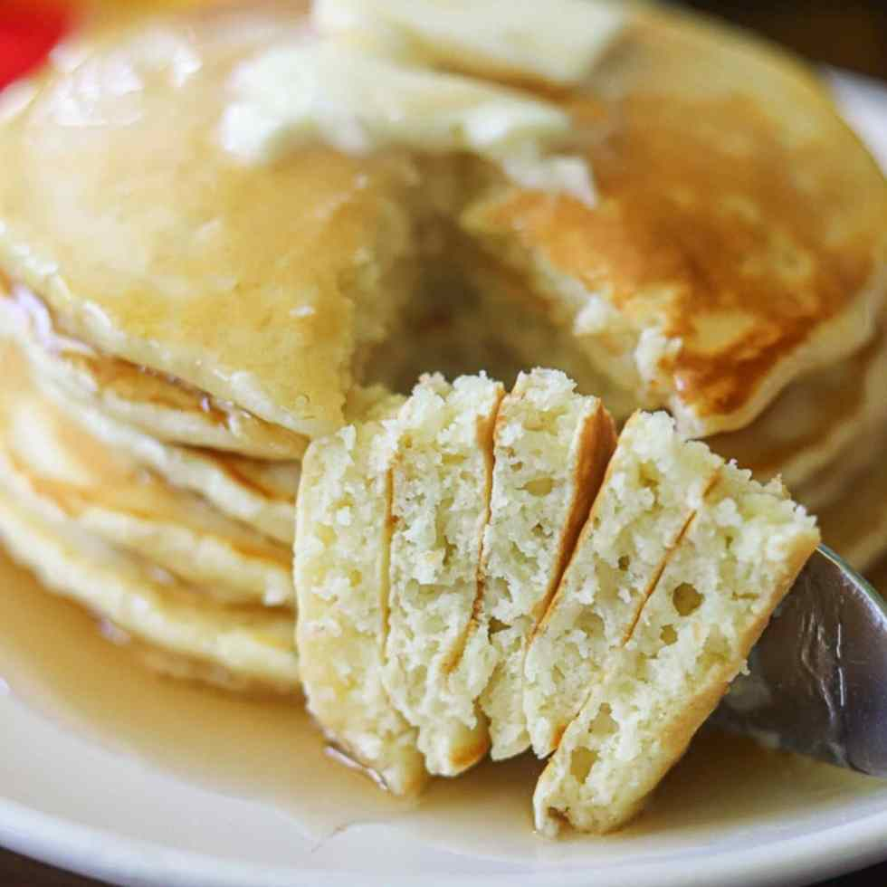 A stack of light and fluffy classic pancakes on a white plate topped with butter and syrup and one bite taken.