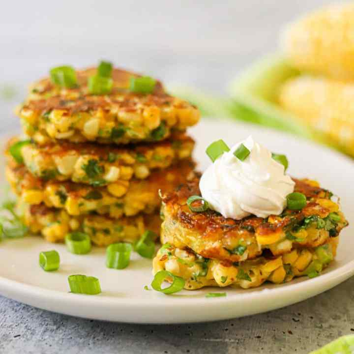 a plate full of golden Thai Corn fritters topped with sour cream and fresh chopped green onions