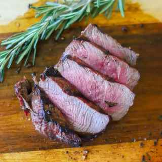 a medium rare London broil sliced against the grain, on a wooden cutting board with a sprig of fresh rosemary on the side.