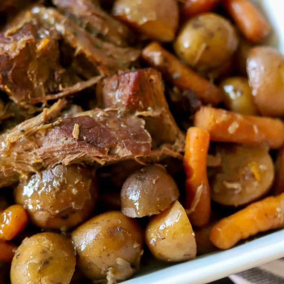 pot roast in a white pan with beef, carrots, and potatoes