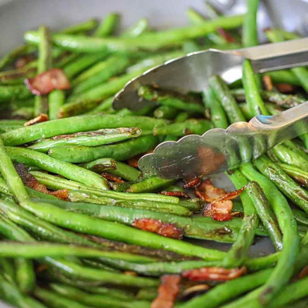 a close up shot of sautéed green beans with bacon and garlic.