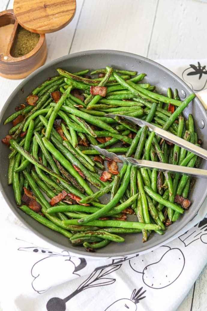 Fresh green beans in a sauté pan tossed with crisp bacon and toasted garlic.