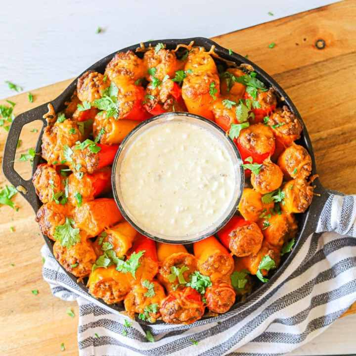 A ring of mini taco stuffed peppers in a cast iron skillet with a bowl of queso dip in the center