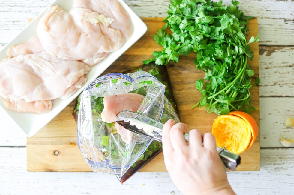 Raw boneless, skinless chicken breasts being placed onto a bag full of orange and cilantro marinade