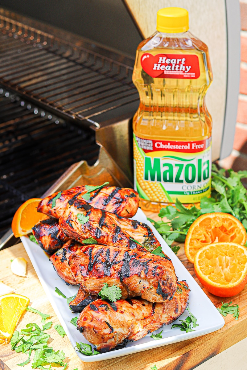 a plate filled with grilled chicken breast sitting on the side of a grill.