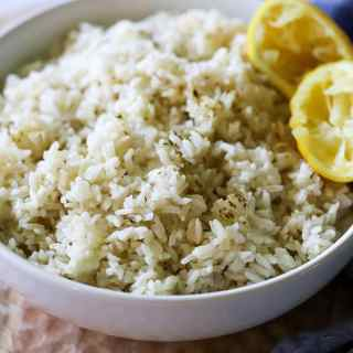 a white bowl full of greek inspired rice garnished with lemon wedges