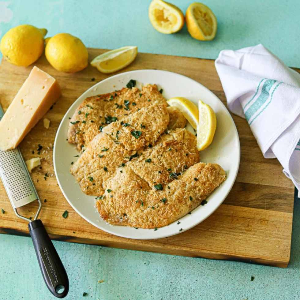 Baked tilapia on a white plate with lemon and fresh parmesan cheese off to the side.
