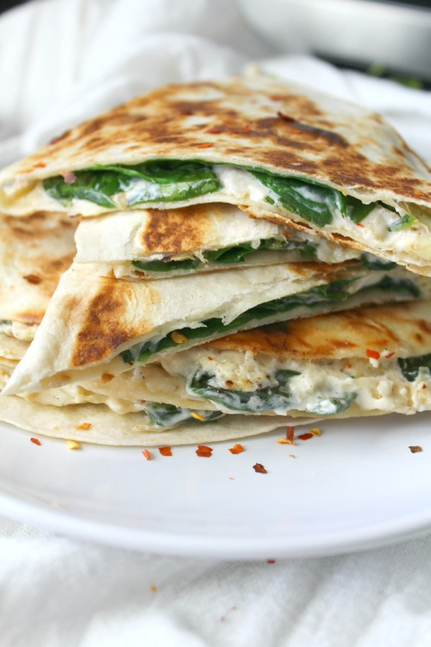 Two favorite snacks are combined into one with these Vegan Spinach Artichoke Quesadillas. These are ooey, gooey and super delicious | ThisSavoryVegan.com