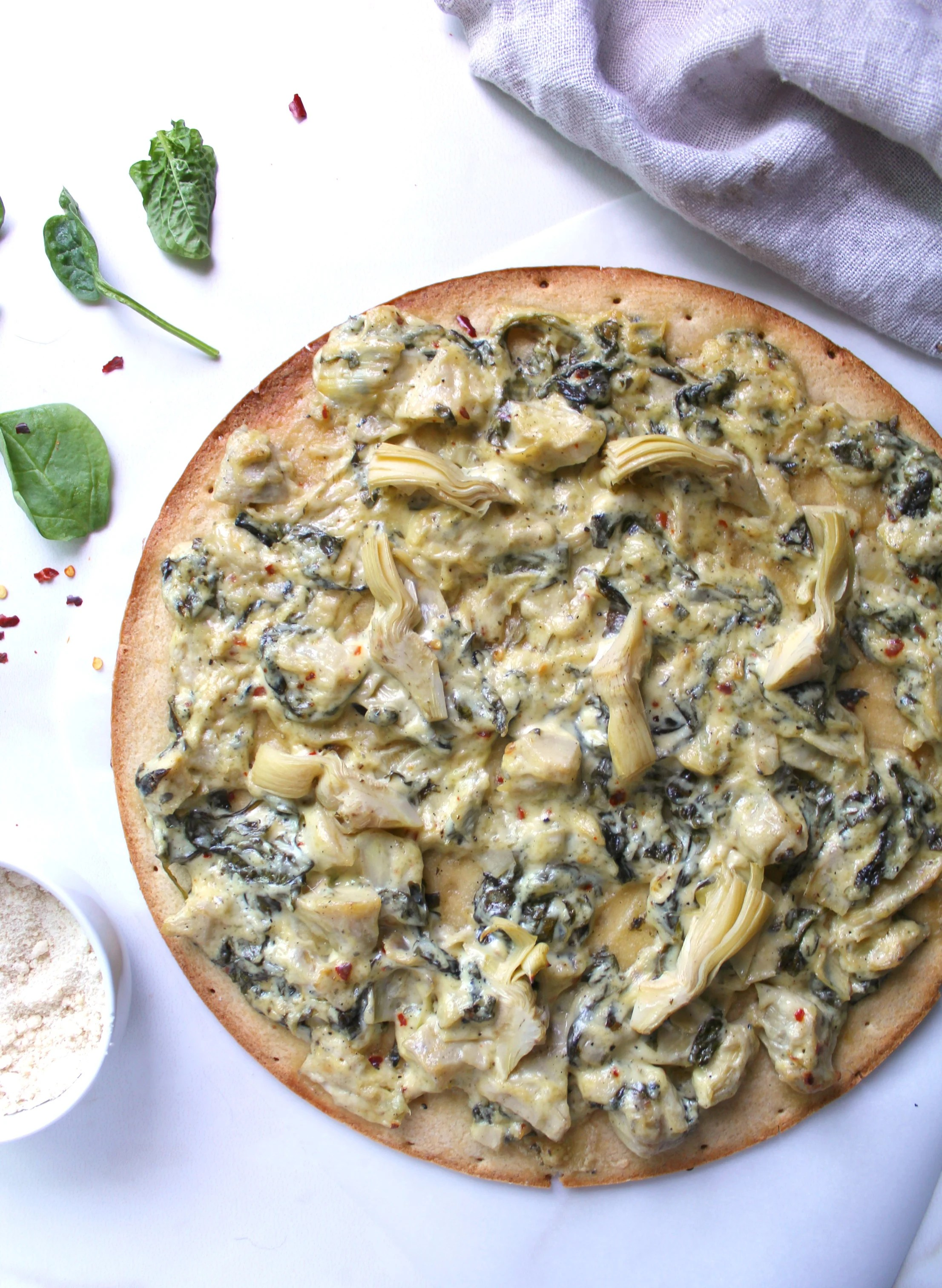 Creamy, comforting and tasty spinach artichoke dip on top of a crispy crust makes this Vegan Spinach Artichoke Pizza an instant favorite | ThisSavoryVegan.com