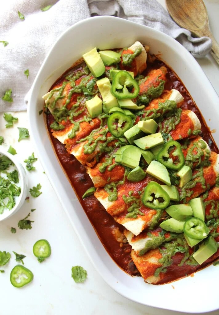 Simple and delicious, these Black Bean Potato Vegan Enchiladas with Avocado Cilantro Sauce are the perfect weeknight dinner! | ThisSavoryVegan.com