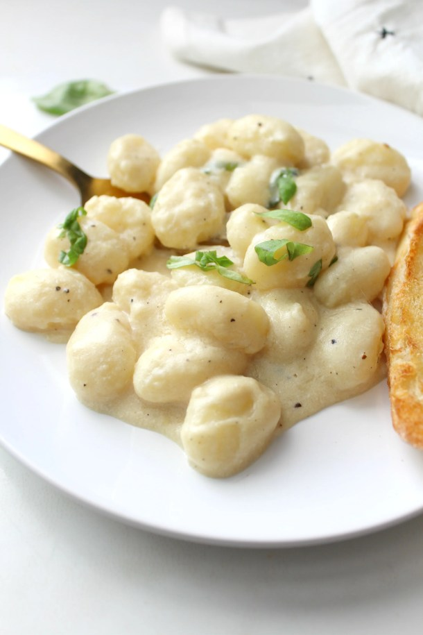ThisCreamy White Wine Vegan Gnocchi is a rich and simple meal that will have you coming back for more. Ready in just 20 minutes!   ThisSavoryVegan.com #vegan #plantbased #pasta