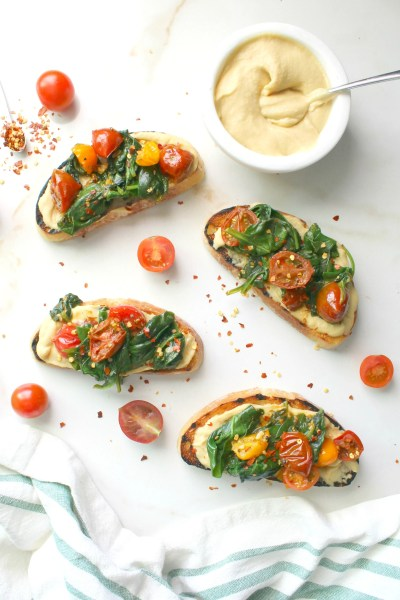 Spruce up breakfast or brunch with this Hummus Toast with Wilted Spinach & Tomatoes. A delicious combination of flavors that will take your toast game to new levels | ThisSavoryVegan.com #vegan #brunch