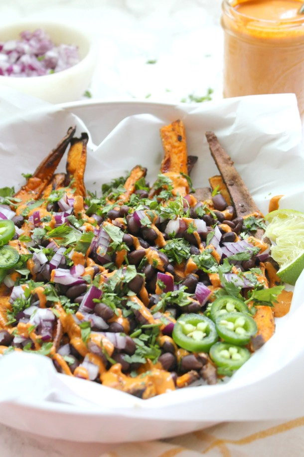 These Loaded Sweet Potato Fries with Vegan Chipotle Sauce are the perfect party snack. Sweet potato fries are baked until crispy then topped with beans, red onion, cilantro and a spicy chipotle tahini sauce | ThisSavoryVegan.com #thissavoryvegan #loadedfries #vegan