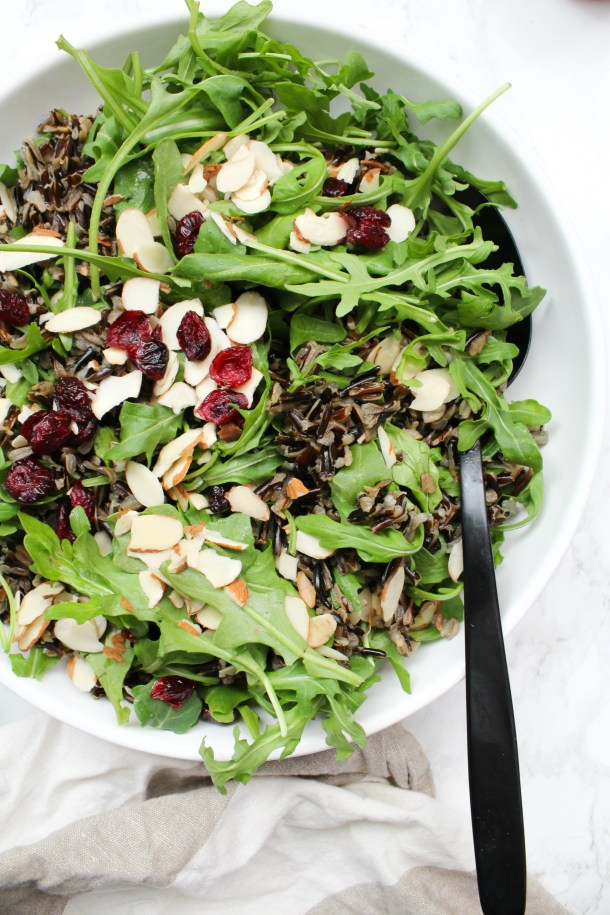 This Wild Rice Arugula Salad is topped with sliced almonds, dried cranberries & a homemade vinaigrette. Perfect winter salad   ThisSavoryVegan.com #thissavoryvegan #vegansalad