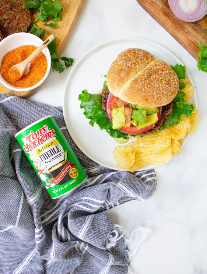 These Vegan Cajun Black Bean Burgers are loaded with a zesty patty, cajun aioli and an avocado salsa. The ultimate combo of flavors | ThisSavoryVegan.com #thissavoryvegan #veganburger #TonyChacheres #CreoleCanDo #ad