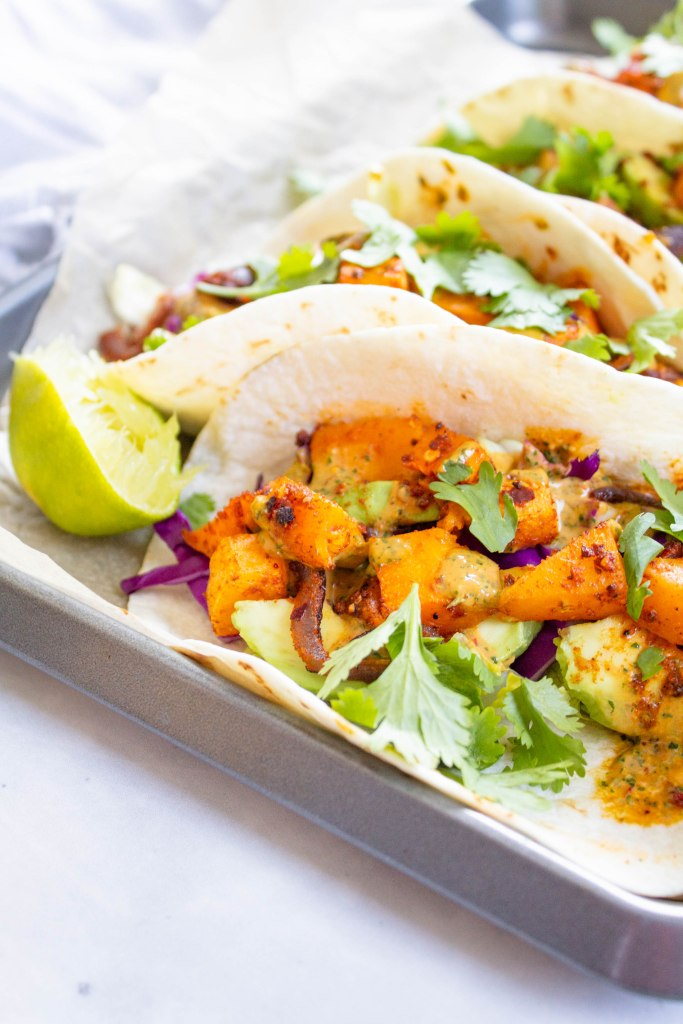 These Vegan Butternut Squash Tacos with Chipotle Cilantro Sauce are a healthy mix of roasted veggies, crunchy toppings and spicy sauce | ThisSavoryVegan.com #thissavoryvegan #vegantacos #tacotuesday