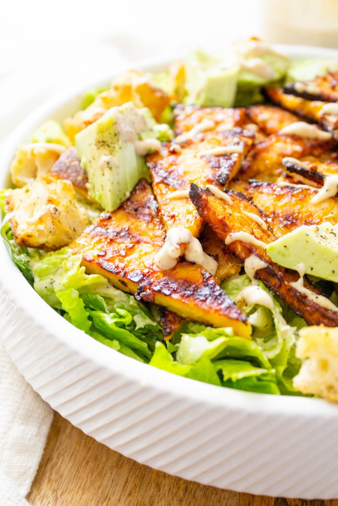 This Grilled Tempeh Vegan Caesar Salad is lightened up by using a tahini-based dressing and protein-packed with marinated tempeh | ThisSavoryVegan.com #thissavoryvegan #vegancaesar #salad
