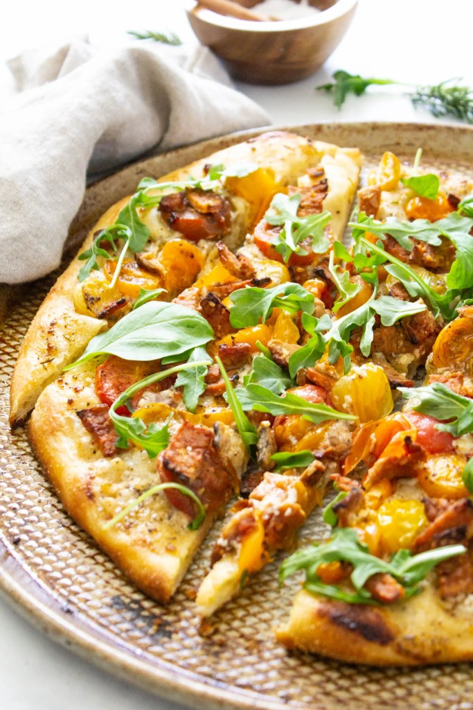 This Vegan BLT Pizza is layered with a rosemary cream sauce, heirloom cherry tomatoes, tempeh bacon and arugula. A fun twist on a classic | ThisSavoryVegan.com #thissavoryvegan #veganpizza #blt