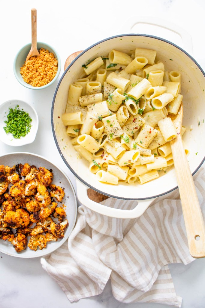 This Creamy Vegan Rigatoni with Roasted Cauliflower is made with a simple and delicious cream sauce, plenty of fresh herbs, and crispy roasted cauliflower. A tasty vegan dinner that is a crowd pleaser | ThisSavoryVegan.com #thissavoryvegan #veganpasta #vegandinner