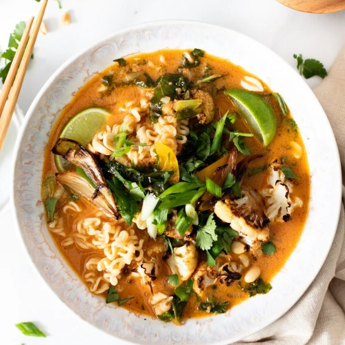 This Vegan Thai Peanut Ramen is packed with flavor and loaded up with noodles, crispy cauliflower, roasted shallots and tons of fresh toppings | ThisSavoryVegan.com #thissavoryvegan #veganramen #thairamen