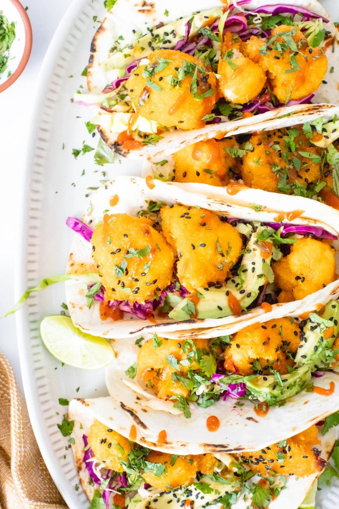These Vegan Bang Bang Cauliflower Tacos are slightly spicy and a whole lotta delicious! A tangy slaw, crispy cauliflower and avocado slices | ThisSavoryVegan.com #thissavoryvegan #vegantacos #cauliflowertacos