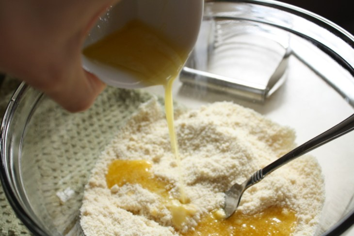 pouring butter into gluten free crust dry mixture