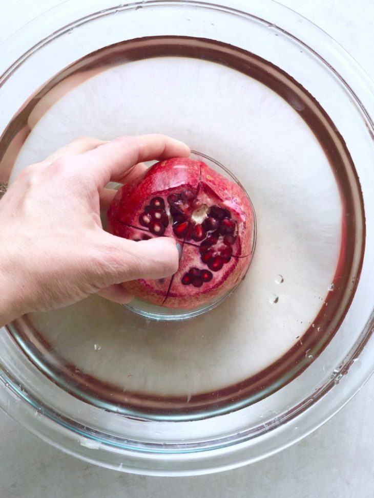 Pomegranate being peeled in bowl of water