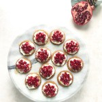 ginger snap topped with mascarpone cheese, fresh pomegranate and honey