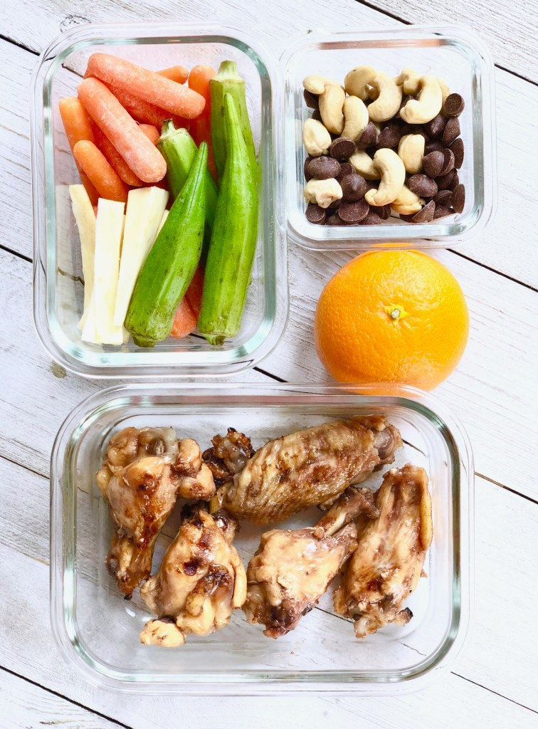 grilled chicken wings, fresh veggies, an orange, chocolate chips and cashew meal prep