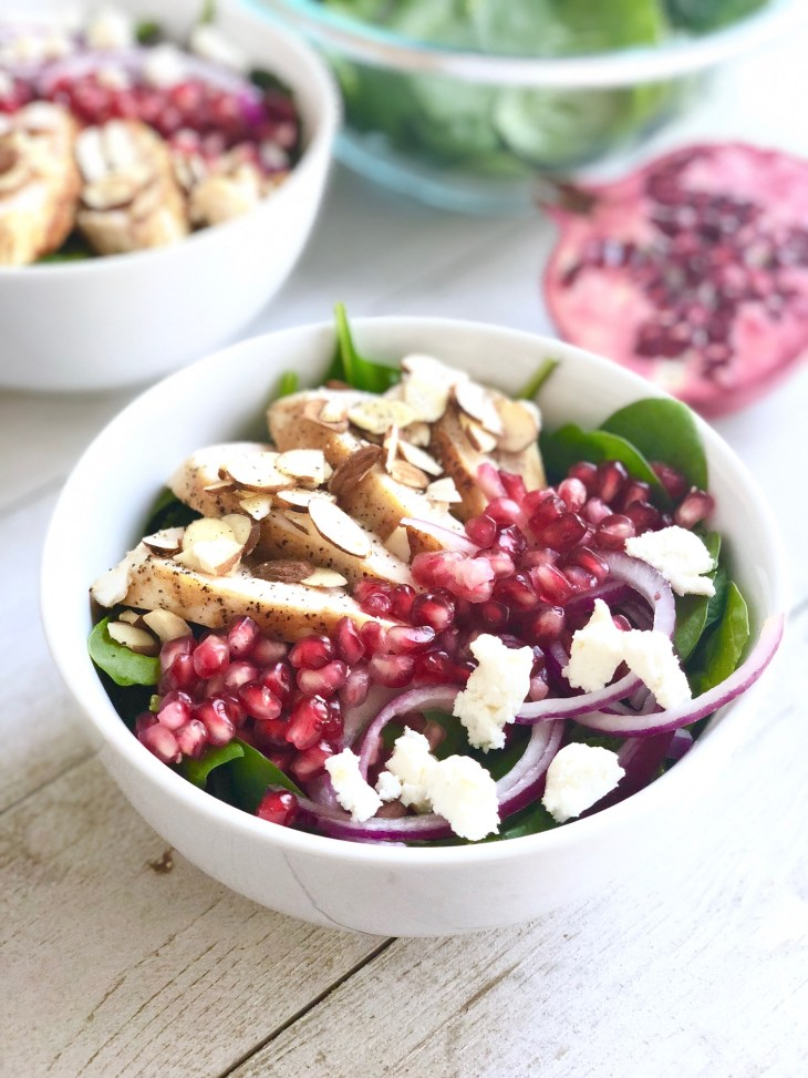 spinach pomegranate salad in a bowl