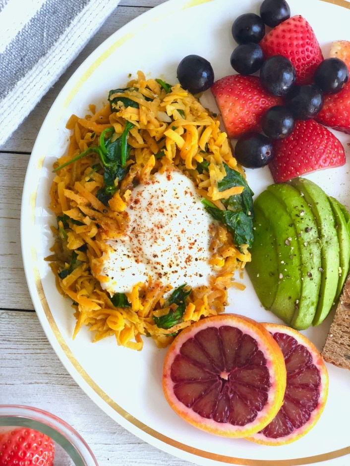 sweet potato hash on a plate with fruit and avocado
