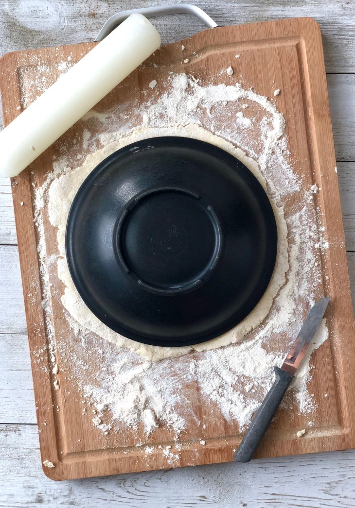 cutting flatbread in a circle using a bowl