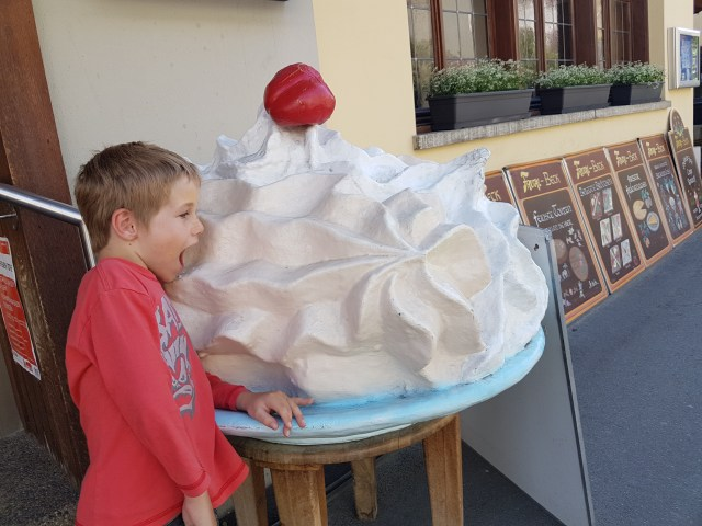 Jetson sampling a huge meringue in Switzerland