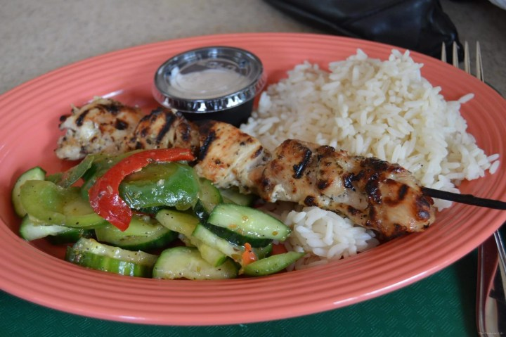 Cucumber salad, chicken skewer and white rice on a coral plate