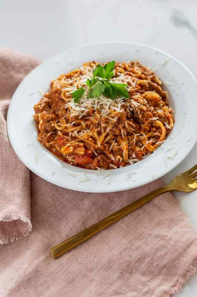 Spaghetti in a white bowl with a light red towel