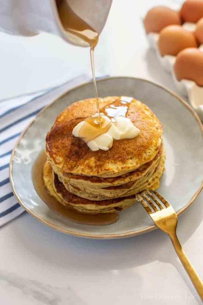 Short stack of pancakes with butter and syrup being drizzled on them